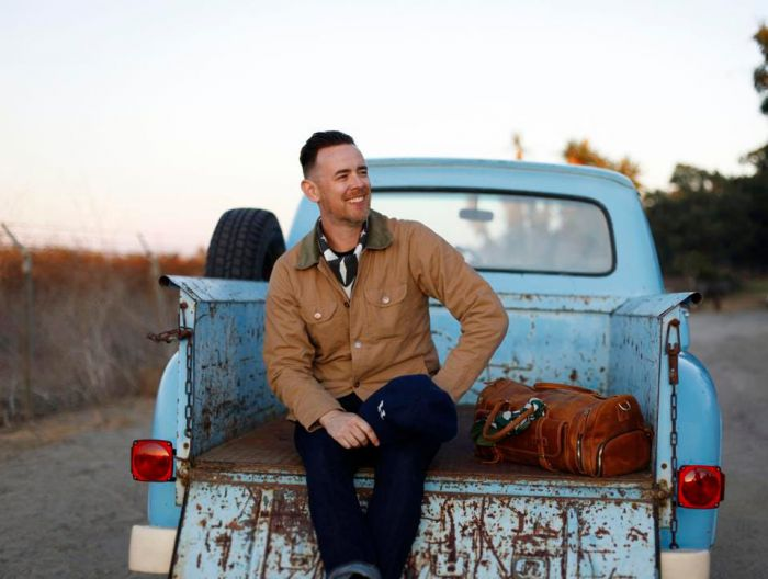 colin hanks sitting in the back of a pickup truck